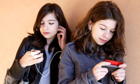 Teens using cell phones and headphones to communicate with friends
